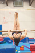 A gymnast in casual athletic clothing is upside down on the uneven bars. The athlete is practicing a routine. Various gymnastics equipment is visible in the background.