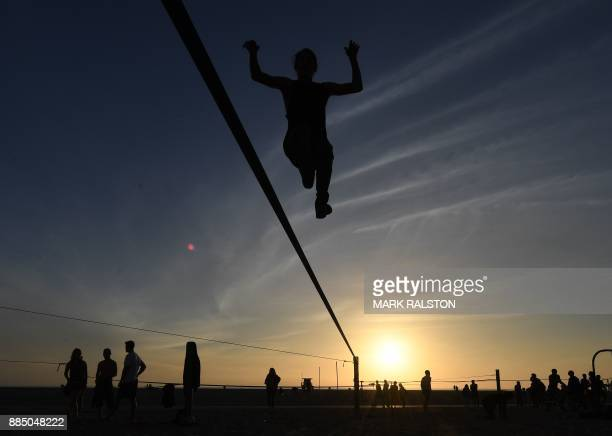 A gymnast practices on a slackline at the original Muscle Beach in Santa Monica California on December 3 2017 The original Muscle Beach was...