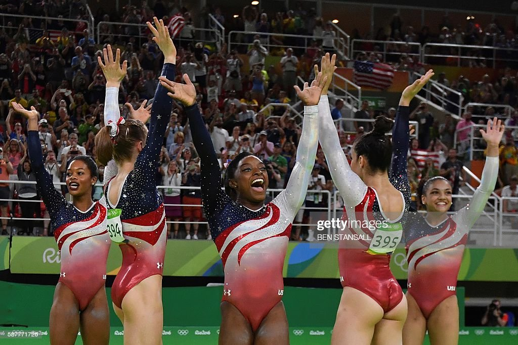 TOPSHOT - US gymnast Simone Biles (C) and her teammates celebrate after winning the women's team final Artistic Gymnastics at the Olympic Arena during the Rio 2016 Olympic Games in Rio de Janeiro on August 9, 2016. / AFP / Ben STANSALL