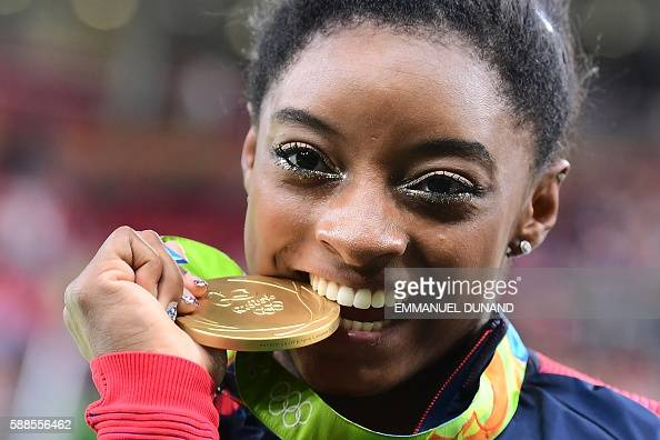 US gymnast Simone Biles celebrates with her gold medal after the women's individual allaround final of the Artistic Gymnastics at the Olympic Arena...