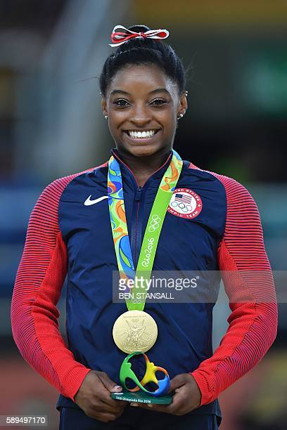 US gymnast Simone Biles celebrates with her gold medal on the podium for the women's vault event final of the Artistic Gymnastics at the Olympic...