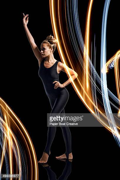 Gymnast standing behind large glowing light