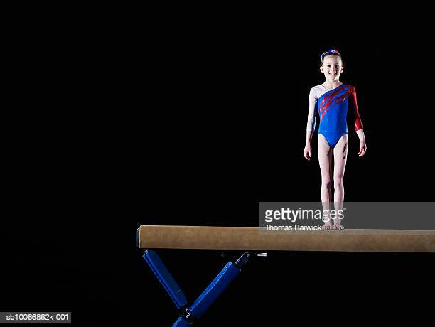 Gymnast (9-10) standing on balance beam