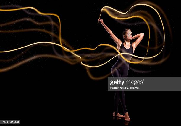 Gymnast waving golden sparkly ribbon