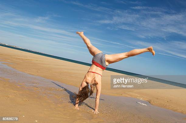 gymnastic girl doing cartwheel on a beach