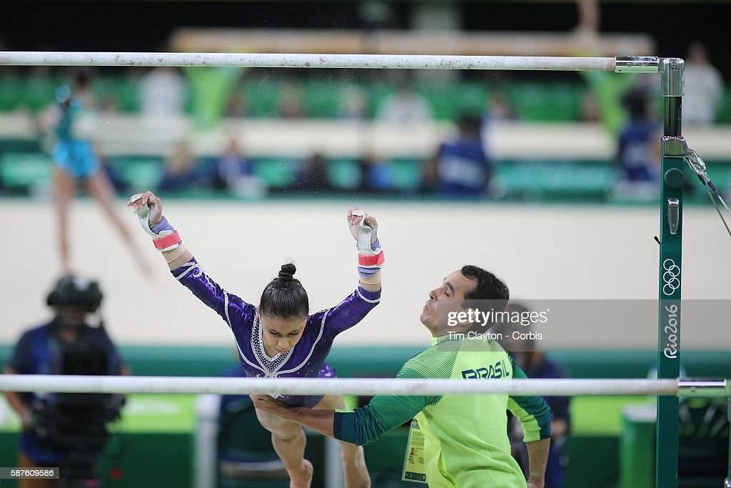 Day 2 Flavia Saraiva of Brazil is caught by her coach Alexandre Carvalho of Brazil as she fall while performing her uneven bars routine during the...