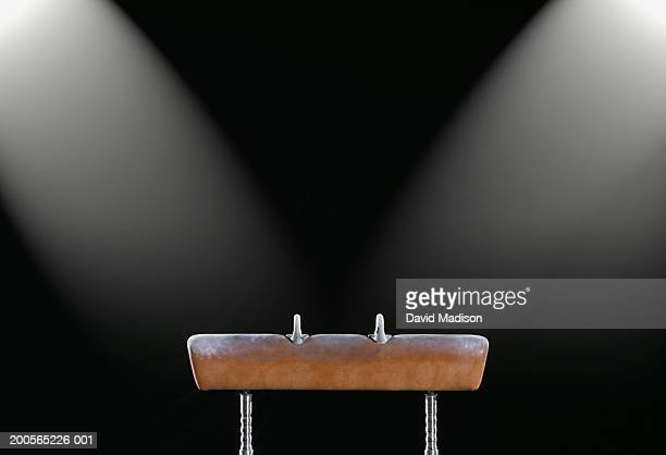 Gymnastics pommel horse illuminated by two spotlights, side view