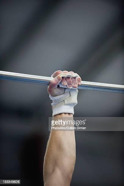 Gymnast's arm holding onto horizontal bar, cropped