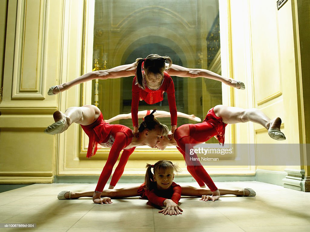 Gymnasts (6-13) balancing in formation in theatre : Stock Photo