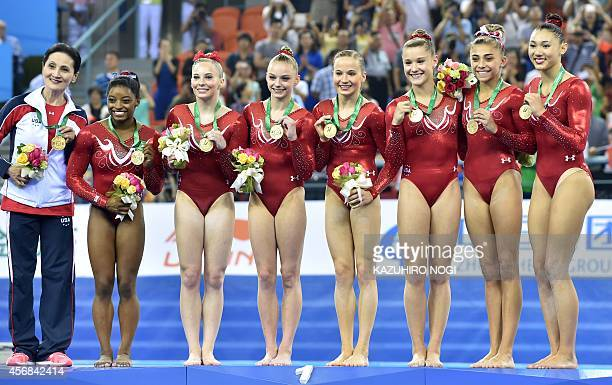 US gymnasts celebrate their victory on the podium during the awards ceremony of the women's team final of the Gymnastics World Championships in...