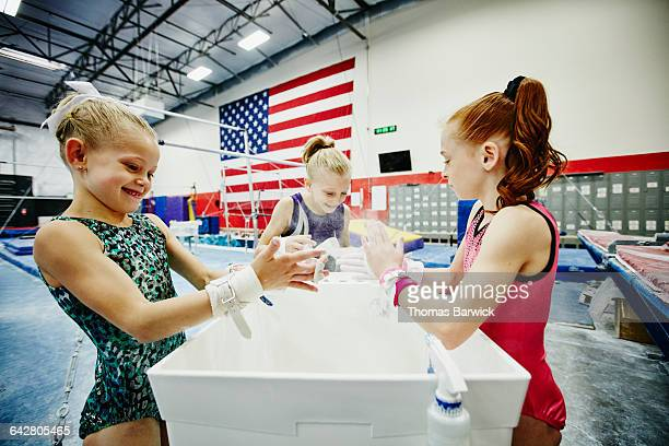 Gymnasts chalking hands during training session