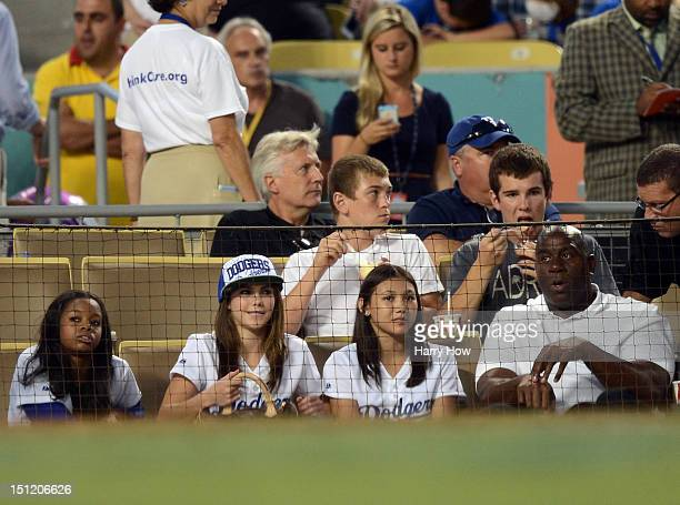 Gymnasts Gabrielle Douglas McKayla Maroney and Kyla Ross sit next to Ervin 'Magic' Johnson during the game between the San Diego Padres and the Los...