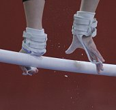 A gymnasts hands on the uneven bars.