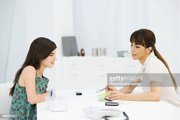 Gynecologist discussing birth control pills with teenage girl