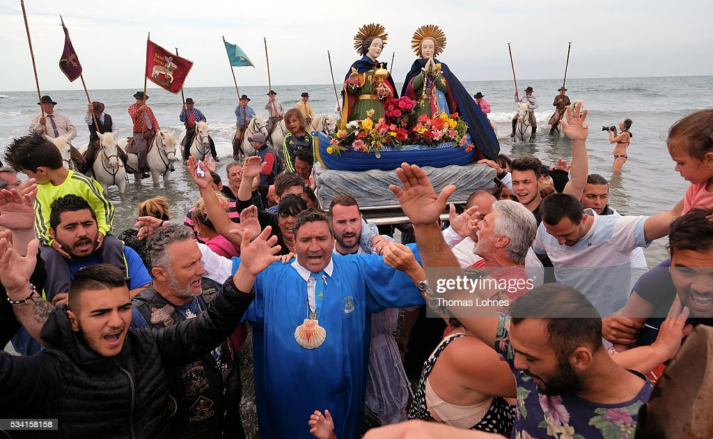 Gypsies and local members of the church carry the sculpture ot Virgin Mary to the sea guardet bei Horses on May 25, 2016 in Saintes-Maries-de-la-Mer near Arles, France. Gypsies from all over Europe worship 'Sara the Black', their Saint and patroness, for one week. Sara's statue is situated in the crypt of the church.