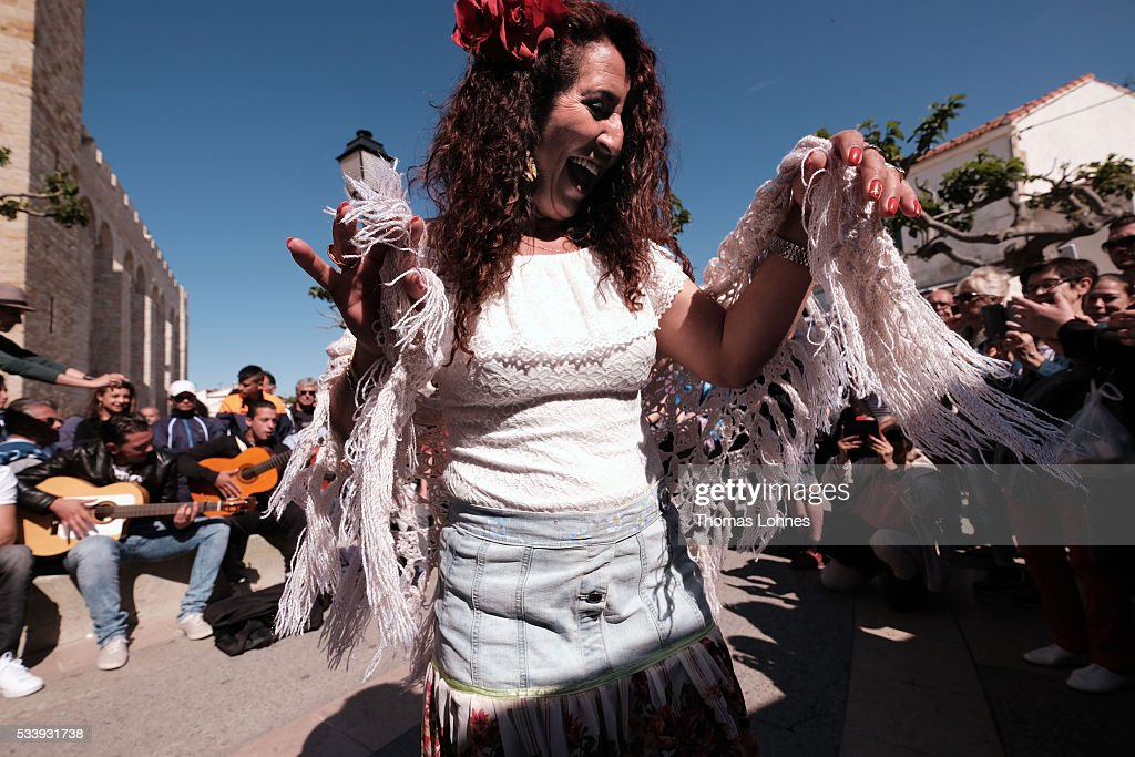 Gypsies dance in front of church to the traditional music of gitares on May 24, 2016 in Staintes Maries de la Mere near Arles, France. Gypsies from all over Europe worship 'Sara the Black', their Saint and patroness, for one week. Sara's statue is situated in the crypt of the church. She wears a multicoloured dress and will carried by the gypsies to the sea at this afternoon.