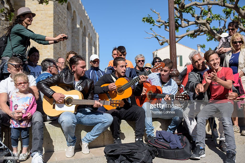 Gypsies play guitars in front of the church on May 24, 2016 in Staintes Maries de la Mere near Arles, France. Gypsies from all over Europe worship 'Sara the Black', their Saint and patroness, for one week. Sara's statue is situated in the crypt of the church. She wears a multicoloured dress and will carried by the gypsies to the sea at this afternoon.
