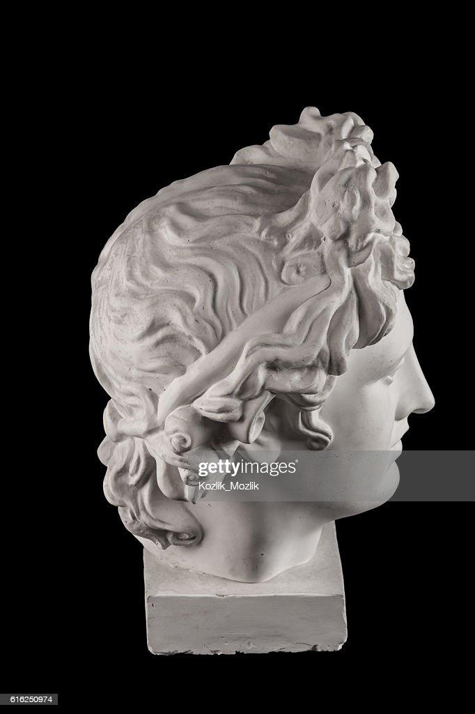 Gypsum statue of Apollo's head on a black background : Foto de stock