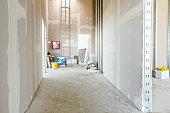 View through corridor of gypsum, plasterboard walls under construction.