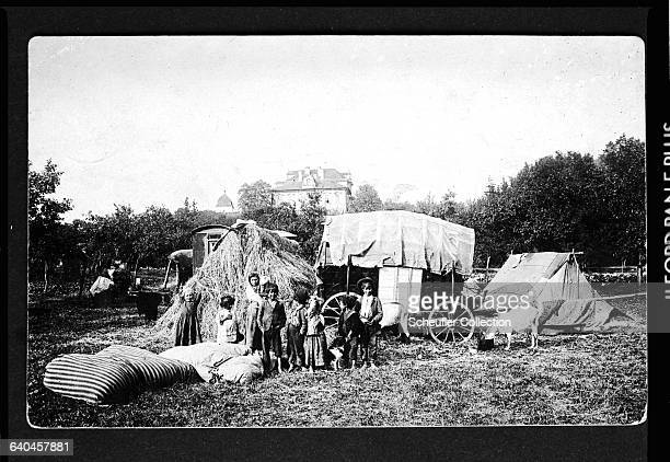A gypsy family comprising a mother with her children stand outside their caravan and tent | Location Czech Lands
