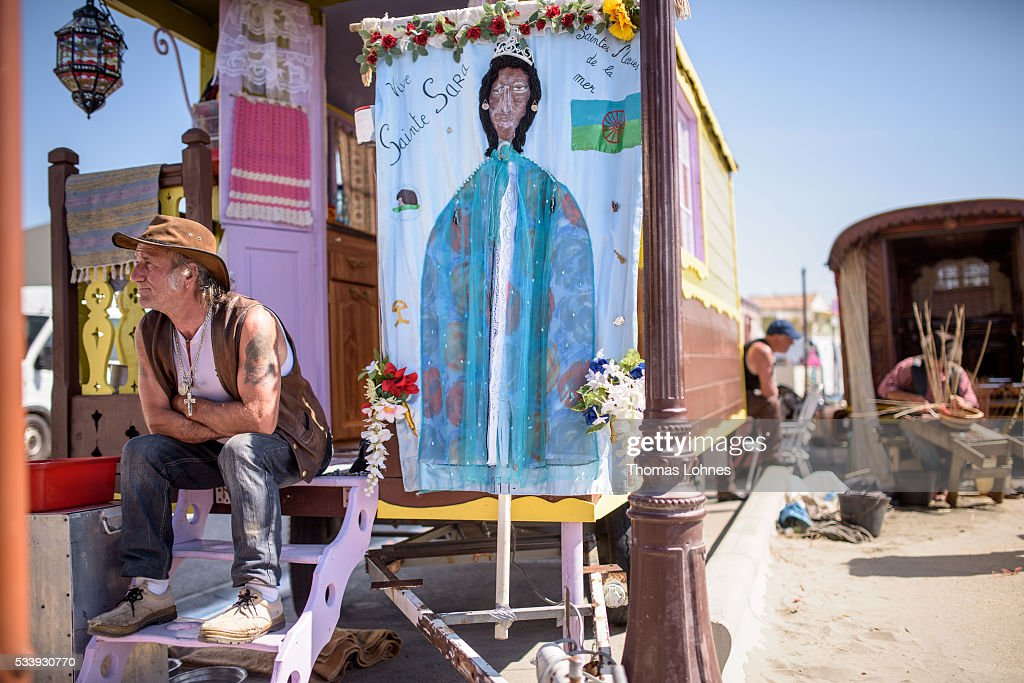 A gypsy sit in in front of his wagon with a painting of 'Sara the Black' on May 24, 2016 in Staintes Maries de la Mere near Arles, France. Gypsies from all over Europe worship 'Sara the Black', their Saint and patroness, for one week. Sara's statue is situated in the crypt of the church. She wears a multicoloured dress and will carried by the gypsies to the sea at this afternoon.