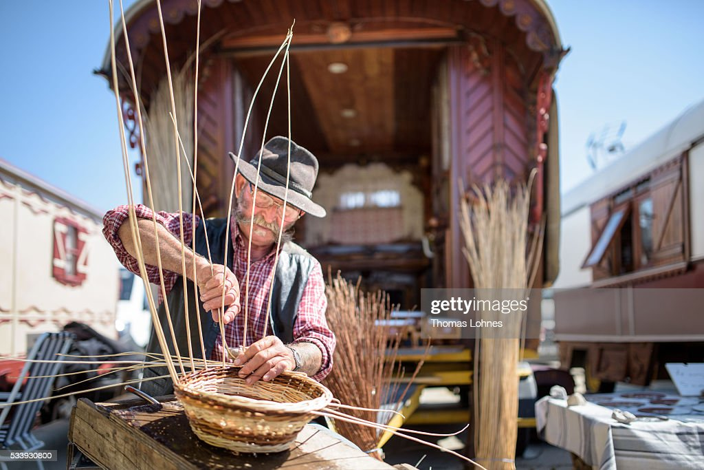 A gypsy weaves a cup in front of his wagon with a painting of 'Sara the Black' on May 24, 2016 in Staintes Maries de la Mere near Arles, France. Gypsies from all over Europe worship 'Sara the Black', their Saint and patroness, for one week. Sara's statue is situated in the crypt of the church. She wears a multicoloured dress and will carried by the gypsies to the sea at this afternoon.
