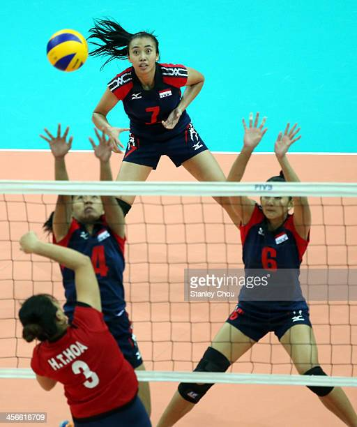 Ha Thi Hoa of Vietnam spikes against Koman and Maya of Indonesia during the Women's Volleyball Team Composition during the 2013 SEA Games at the...