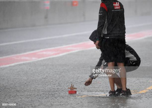Haas F1's mechanics float a small boat during heavy rain in the second practice session of the Formula One Japanese Grand Prix at Suzuka on October 6...