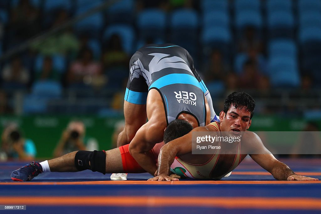 Habibollah Jomeh Akhlaghi of the Islamic Republic of Iran and Denis Kudla of Germany compete during the Men's GrecoRoman 85 kg Repechage on Day 10 of...