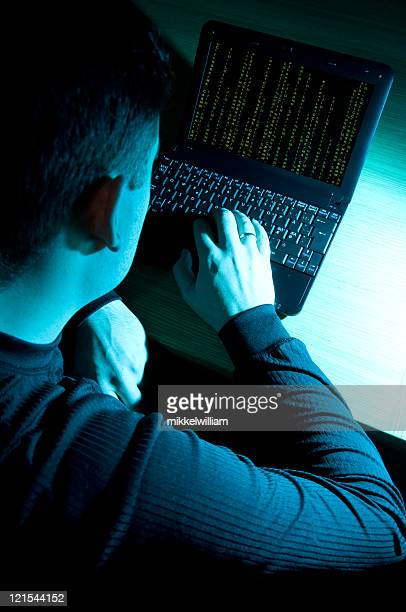 Hacker at work in front of a laptop computer