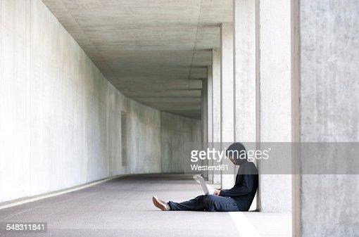 Hacker with laptop sitting in an underground car park