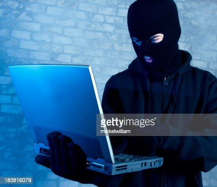 Hacker works on laptop at night
