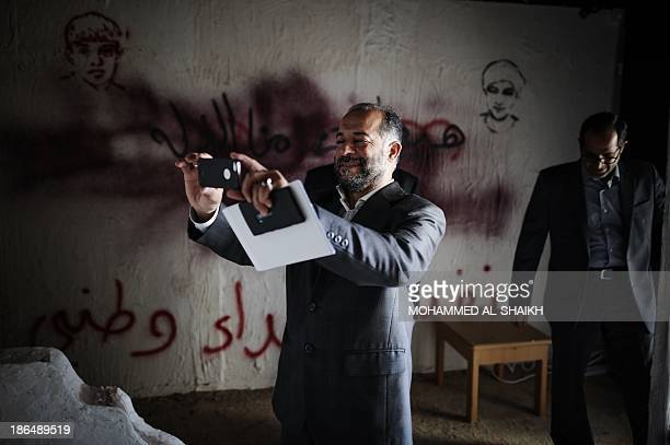 Hadi alMosawi a former Bahraini MP from the opposition group alWefaq Society uses his mobile phone to take a picture of the 'revolution museum' on...