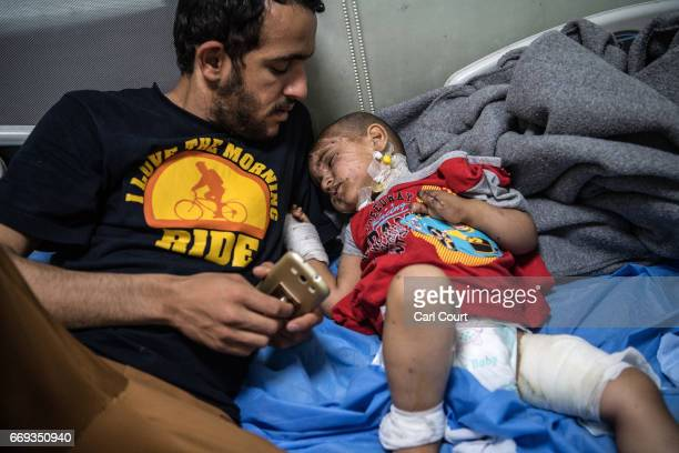 Hadi Talib comforts his neighbour's child three year old Eslam Ahmad who along with his mother and father received serious injuries after an improved...