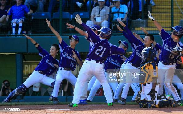 Hae Chan Choi of Team AsiaPacific celebrates with teammates after hitting a solo home run against the Great Lakes Team from Chicago Illinois during...