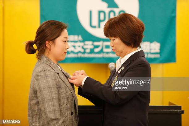 HaeRym Kim of South Korea receives a lapel pins from LPGA Hiromi Kobayashi during the Ladies Professional Golfers' Association of Japan induction...
