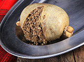Scottish Haggis Cooked For A Burns Night Dinner Against A Royal Stuart Tartan