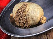 Scottish Haggis Cooked For A Burns Night Dinner Against A Royal Stuart Tartan