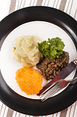 typical scottish dish, haggis with mashed potato, turnip and parsley on a plate
