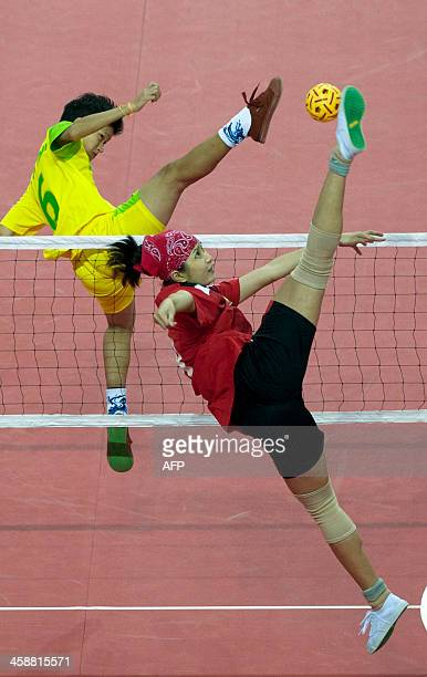 Hai Thao Nguyen of Vietnam returns the ball to Myanmar's Phyu Phyu Than during the women's double team sepaktakraw final event at the 27th Southeast...