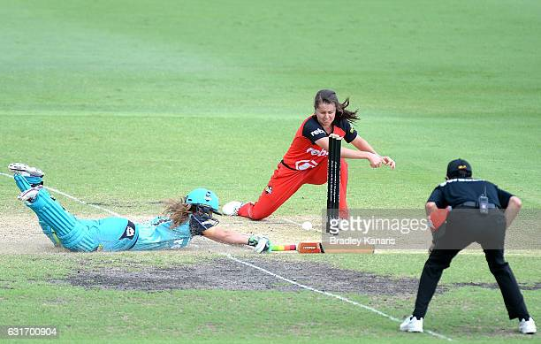 Haidee Birkett of the Heat makes her ground as Molly Strano of the Renegades loses control of the ball during the Women's Big Bash League match...