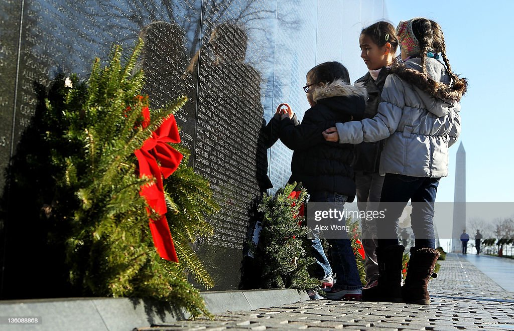 Hailey Hughes (C) of San Antonio, Texas, visits the Vietnam Veterans Memorial with cousins Isabella Santucci (R) and Samantha Santucci (L) of Fullerton, California, December 19, 2011 in Washington, DC. The Vietnam Veterans Memorial Fund (VVMF) honored veterans and active-duty military personnel during its annual Christmas tree ceremony by placing the tree, decorated with homemade holiday greeting cards and ornaments sent by Americans, near the wall of the memorial.