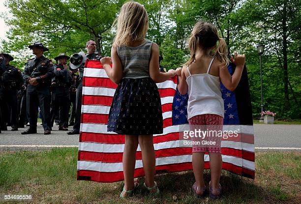 Hailey Wilson left and her sister Suri Wilson daughters of State Police Lieutenant David Wilson Sr hold an American flag while paying respect to the...