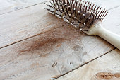 Hair loss, Close up of hairbrush with lost hair on wood table