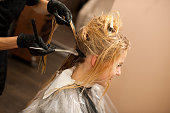 hair stylist at work - hairdresser  applying a color on   customers  hair after haircut and before doing hairstyle in a professional studio