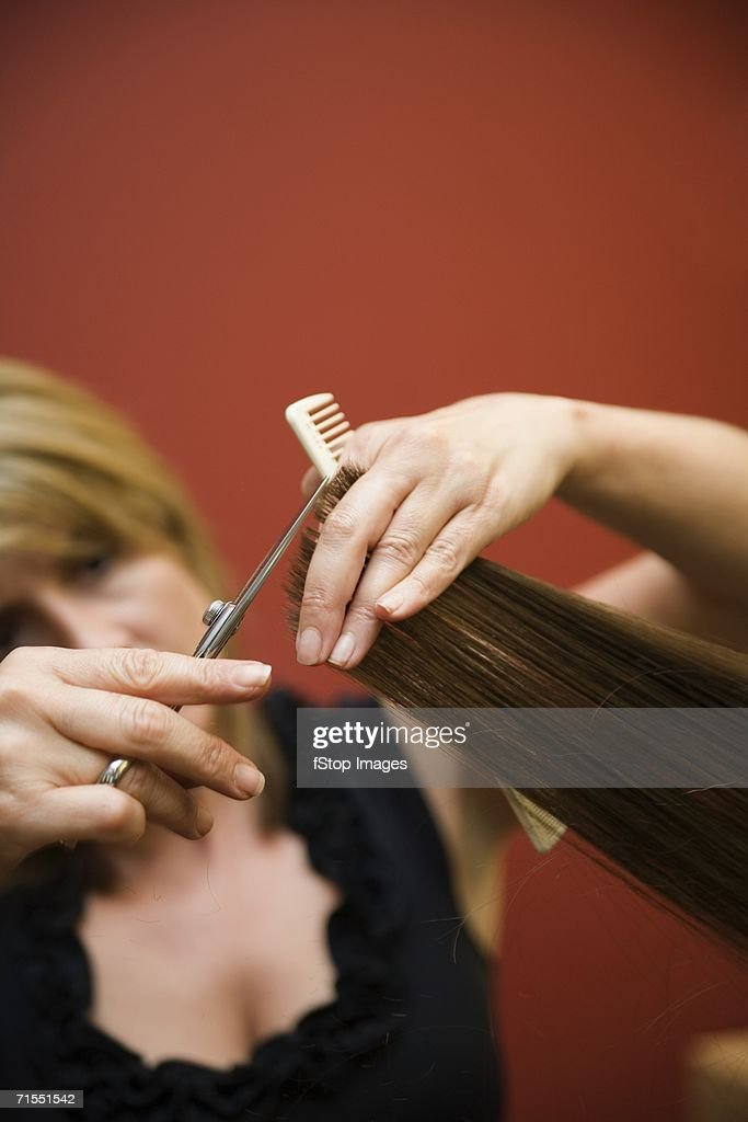 A hair stylist cutting a woman?s hair : Stock Photo