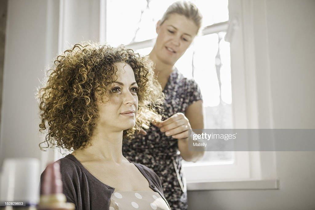 Hair stylist working on client