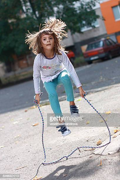 Hair tossed girl (6-7) with jumping rope