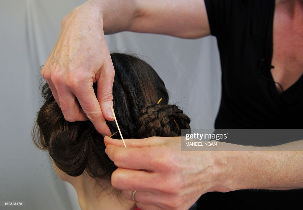 Hairdress Janet Stephens (R) works on the hair of model Jackie Rose Womelsdorf to recreate the hairstyle worn by Roman Empress Faustina on February 25, 2013 in Baltimore, Maryland. AFP PHOTO/Mandel NGAN