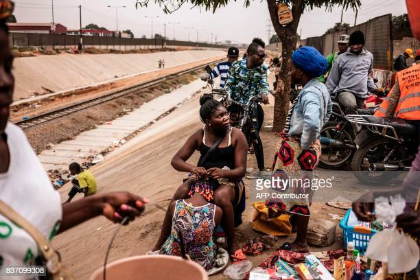 A hairdresser applies hair extensions to a customer on top of the containment walls of a train track in the Viana district in Luanda on August 22...
